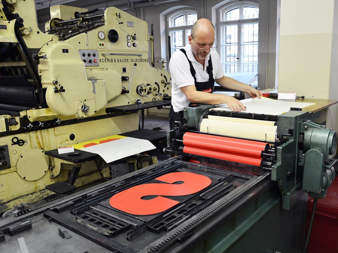 Hochdruck_Druck mit Riesen-Holzbuchstabe auf einer hist. Abziehpresse (c) Museum für Druckkunst Leipzig